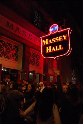 Exterior view of main entrance and neon signage of Massey Hall at night