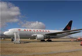 Side view of a parked Air Canada twin-engine jet in the desert, with stairs mounted next to the aircraft's forward door.