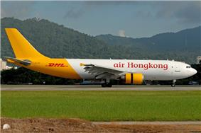 An aircraft painted in white colour with the name Air Hong Kong painted in red on the fuselage, and in yellow colour from the rear to the tail with the name DHL painted in red on the tailfin.