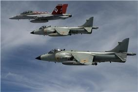 Two similar grey jet aircraft with high-mounted wing flying in formation with another red-tail fighter, which is leading and is furthest from photo. The leading jet is carrying an external fuel tank under fuselage.