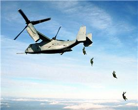 color photo of four parachutists jumping from the open ramp of an MV-22 Osprey in flight