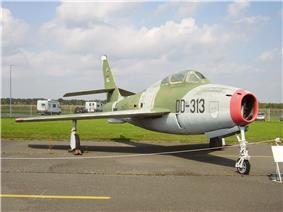 A camouflaged jet aircraft with a red ring around its nose intake, on display