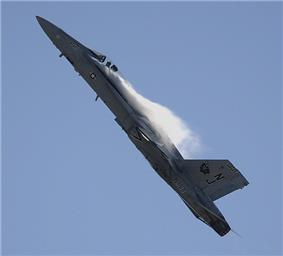 Jet fighter aircraft is seen against blue sky executing a pull-up, making it nearly vertical with contrail formed aft of the canopy.