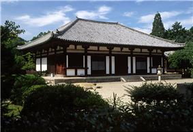 Wooden building on a stone platform with white walls.