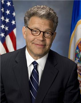 Head and shoulders portrait of man in his forties with close-gray hair in a business suit and tie with a U.S. and Minnesota flag in the background