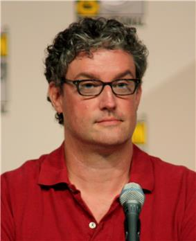 A man with glasses and a red shirt sits in front of a microphone.