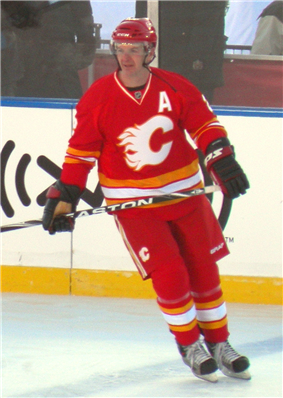 An ice hockey player looks to his right as he glides across the ice.  He is in a red uniform with white and yellow trim, with a stylized