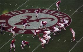 American football players in formation waiting for the snap at midfield.