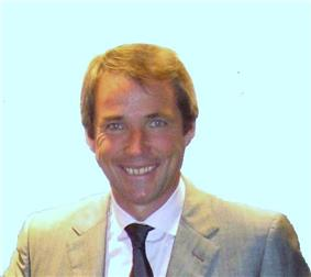 Head-and-shoulders photograph of Alan Hanson, who is wearing a grey suit, white shirt and black tie.