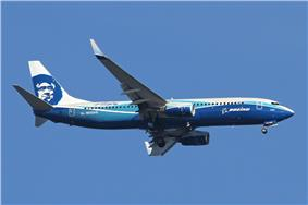 Right side view of an aircraft painted blue on the fuselage in Boeing's corporate livery, with Alaska Airlines' Eskimo face on the tail. The aircraft is airborne in blue skies.