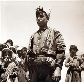 Adolescent boy standing in front of younger children