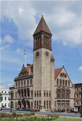A brown and tan brick building with dark brown trim. The building has a tall bell tower on the nearest corner.