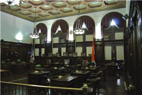 A large room with four arched windows, a bar, and multiple seats for legislators. Walls are wood paneled and the room is lit by two large chandeliers.