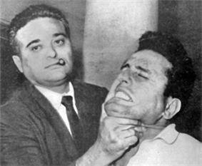 A black-and-white photograph showing a man wearing a jacket and tie with a short sigar in his mouth, on the left, holding up the chin of a man on the right, who appears to be in pain