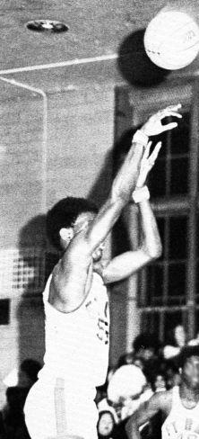 A man, wearing a white jersey, is shooting a basketball.