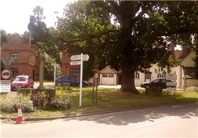 Photograph of a small village green, showing a drinking fountain, oak tree, and well