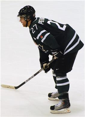 An ice hockey player leaning forward on his ice hockey stick and facing to the left of the camera. He is wearing a black helmet and uniform.