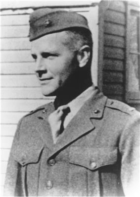 Head and shoulders of a young white man wearing a garrison cap and a plain military jacket over a shirt and tie