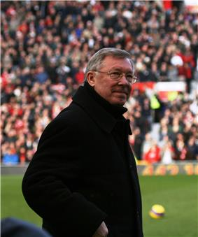 A man wearing a jacket and glasses in a football ground