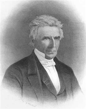 A man in his mid-60s turned a quarter of the way to the right. He's wearing a dark formal suit with a white shirt, high collar and white tie. His hair is white and loosely combed. His expression appears serious but not unfriendly.