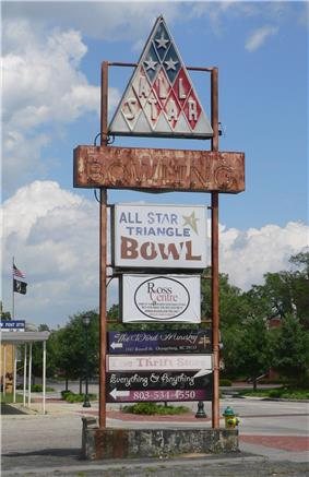 Faded and rusting sign in parking lot: at top, triangular sign with