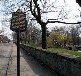The low stone wall is seen running along the 40th Street side of Arsenal Park with the Pennsylvania Historical Marker for the Allegheny Arsenal to the left and, on the right behind some trees, a portion of the low-lying stone powder magazine is visible in the park.