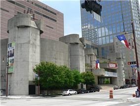Concrete building in two sections, each with a five-sided tower on the ends. One is a curved and windowless. The other looks like a theater entrance with  rounded  marquee shapes and glassed entrance.