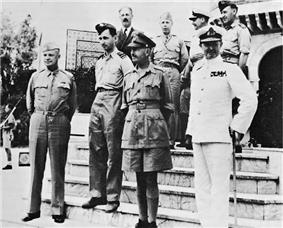 Eight men standing on the steps of a Middle Eastern building. Six are wearing various uniforms but one is wearing a business suit.