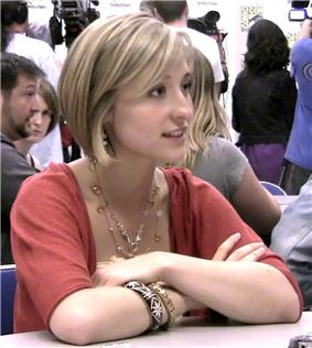 Young, blonde woman with arms folded at a table