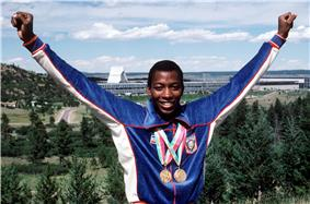 An African-American athlete wearing a blue running top and two gold medals hang from his neck.