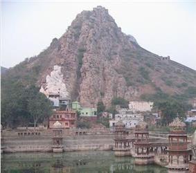 Daytime view of a more-or-less cone-shaped peak, perhaps reaching two hundred feet above the surrounding terrain. It is sparsely covered in poor-looking shrubs and trees; it otherwise reveals only an aspect of heated naked rock. Assorted parti-coloured blocky concrete buildings reach down from its lower slopes to a temple tank in the near foreground, around which is arrayed the more rounded and ornate temple structures.