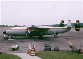 A twin-engine turboprop airliner with three fins parked on ramp while being serviced, with mobile staircases located nearby.