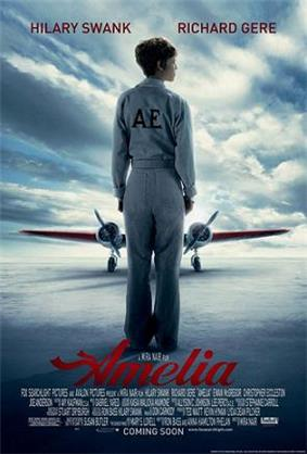 Hilary Swank as Amelia Earhart standing alone on the runway with her back turned wearing a flight suit and an aircraft filling the background
