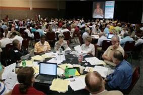 Dozens of people talking at tables in a large room.