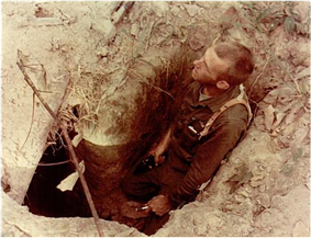 A soldier holding a pistol stands in a hole in the ground before the entrance to a tunnel