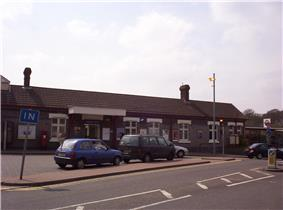 A long building with two chimneys protruding from its roof and four cars driving from left to right across a paved area in the foreground