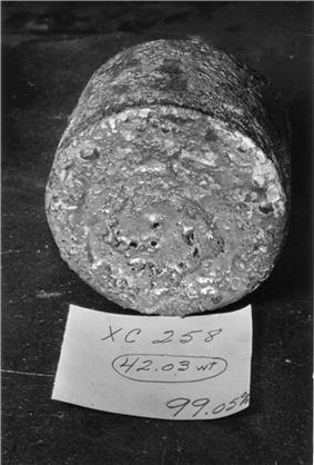 A rough-surfaced cylinder of metal with a paper in front of it, like a label