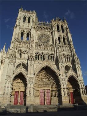 A very tall cathedral with three large entrances.