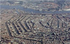 An aerial view of a cramped city, clearly spaced by hexagonal bodies of water.