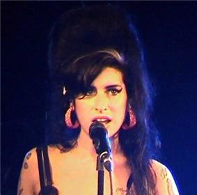 Head and shoulders photograph of Amy Winehouse performing live.