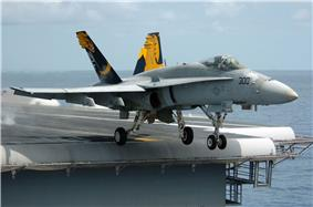 F/A-18 Hornet fighter departing aircraft carrier. A gray-overall aircraft, with blue and yellow fins, has just left the edge of carrier's runway, as evident through the extended landing gear.