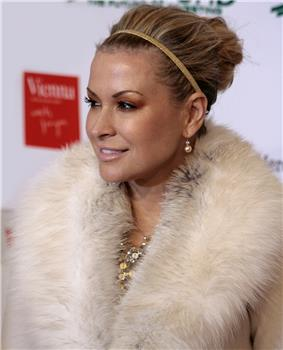 A woman in makeup smiles. Her locks are held back by a hairband, and she wears an elaborate fur-like material arouns her neck.