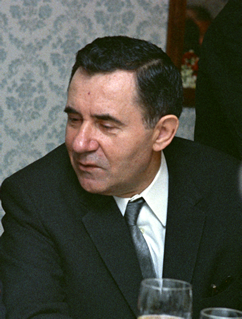 A man in a dark suit, seated, looking to his left