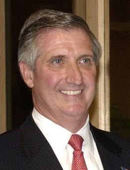 Smiling man wearing a suit and a red tie