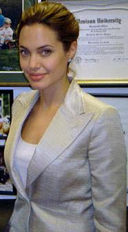 A brown haired woman stands in front of a wall with framed pictures and papers. She wears a light grey jacket over a white top.