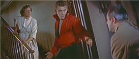 A color screenshot of a woman on the middle of a staircase, a teenager at the bottom, and a man in the front of the staircase. The teenager is wearing a red jacket and has his arms outstretched at his side.