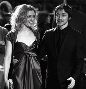 A black and white image of a blonde women wearing a stain dress and dark-haired male standing beside each other. She is looking to her left and holding a clutch purse with her right hand. He is wearing an all-black suit and smiling.