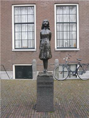A bronze statue of a smiling Anne Frank, wearing a short dress and standing with her arms behind her back, sits upon a stone plinth with a plaque reading