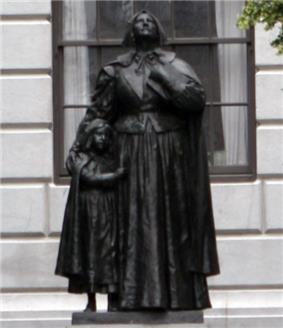 A photograph of a metal statue of a woman standing upright with her head tilted upward and her eyes looking up.  She is dressed in a full dress, and beside her is a young girl who is clinging on to her.