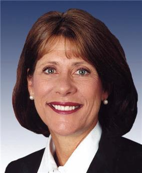 A brown-haired woman in her early fifties wearing a white blouse, black jacket, and pearl earrings